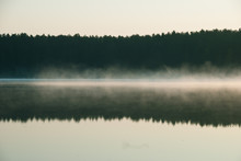 Reflection Of Clouds In Calm Lake In Foggy Weather