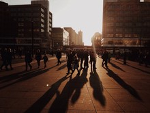 People Walking At Town Square In City During Sunset