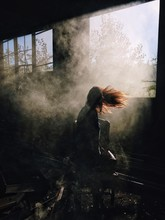 Sunlight Falling On Woman With Tousled Hair At Abandoned Building