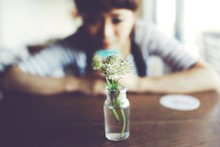 Woman Looking At Flowers In Vase On Table