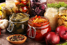 Preserves Vegetables In Glass Jars. Pickled Cucumber, Carrot, Fermented Cabbage And Onions On Rustic Background