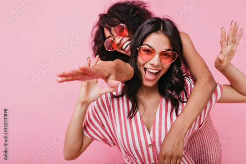 Fotografia Happy, positive girls in light pink summer clothes, posing with sincere smile