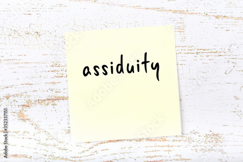 Yellow sticky note on wooden wall with handwritten word assiduity Wallpaper Mural