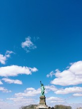 Statue Of Liberty Against Cloudy Blue Sky