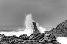 Waves Breaking On Rocks At Overcast Day