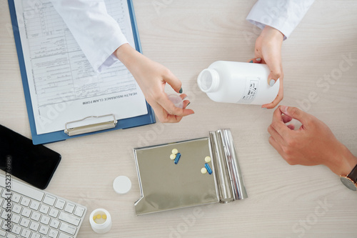 Hands of doctor giving patient some pills and tablets, view from the top