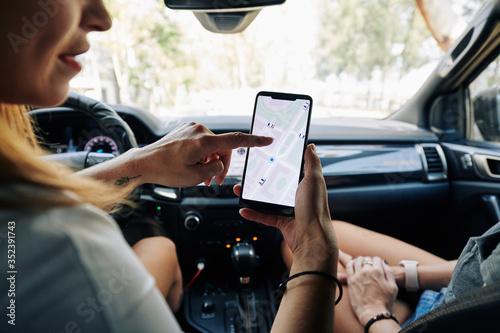 Fototapeta Female friends sitting in car and setting destination point on smartphone application obraz