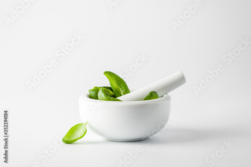 Canvas Print Basil leaves in a mortar on a white background