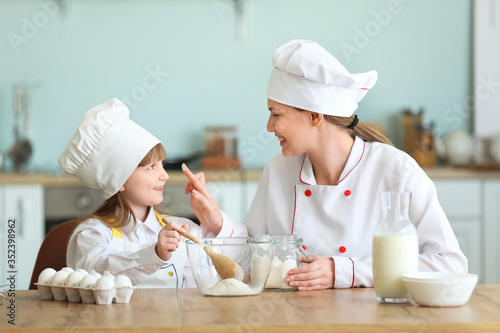 Canvastavla Female chef and her little daughter cooking in kitchen
