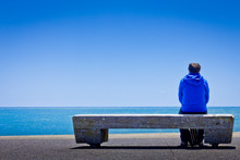 Rear View Of Person Sitting On Bench By Sea Against Clear Blue Sky