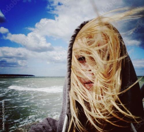 Fotografija Close-up Portrait Of Woman With Windswept Hair On Beach
