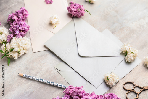 Obraz Composition with beautiful lilac flowers and envelopes on light background - fototapety do salonu