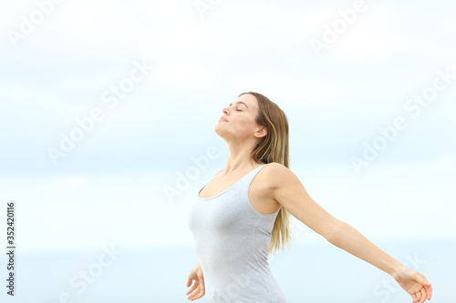 Obraz Woman breathing fresh air at the beach - fototapety do salonu