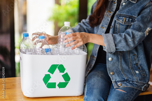 Obraz A woman collecting and separating recyclable garbage plastic bottles into a trash bin at home - fototapety do salonu