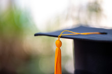 Closeup, Black Graduated Hat And Golden Yellow Tassels And Blurred Background