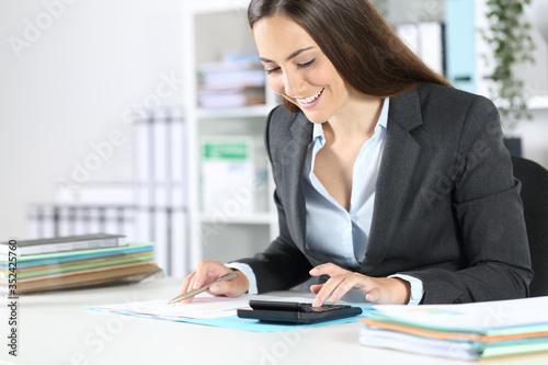 Obraz Bookkeeper calculating on calculator checks document at office - fototapety do salonu