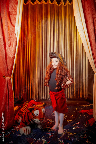 Young girl during stylized theatrical circus photo shoot in beautiful red locati Wallpaper Mural