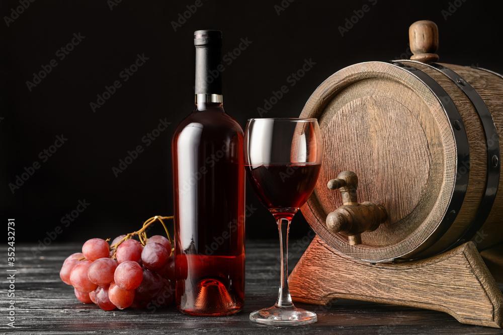 Fototapeta Wooden barrel, bottle and glass of wine on dark background