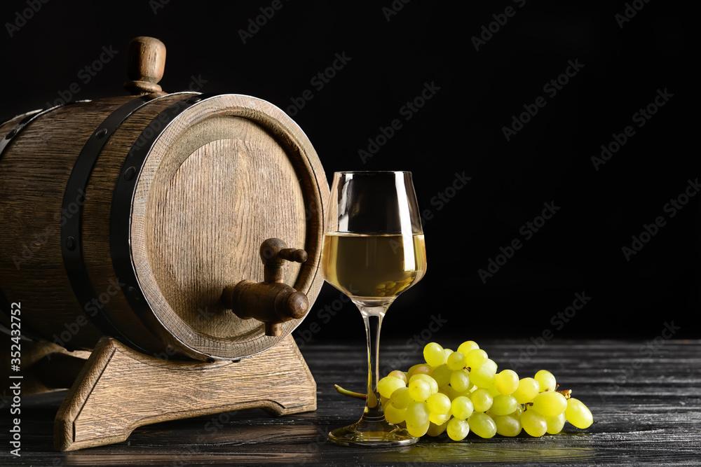 Fototapeta Wooden barrel and glass of wine on dark background