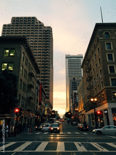Fotomural Cars Moving On City Street Amidst Buildings During Sunset