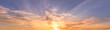 Cloudy sky at sunset or sunrise with bright sun. Abstract background for design.