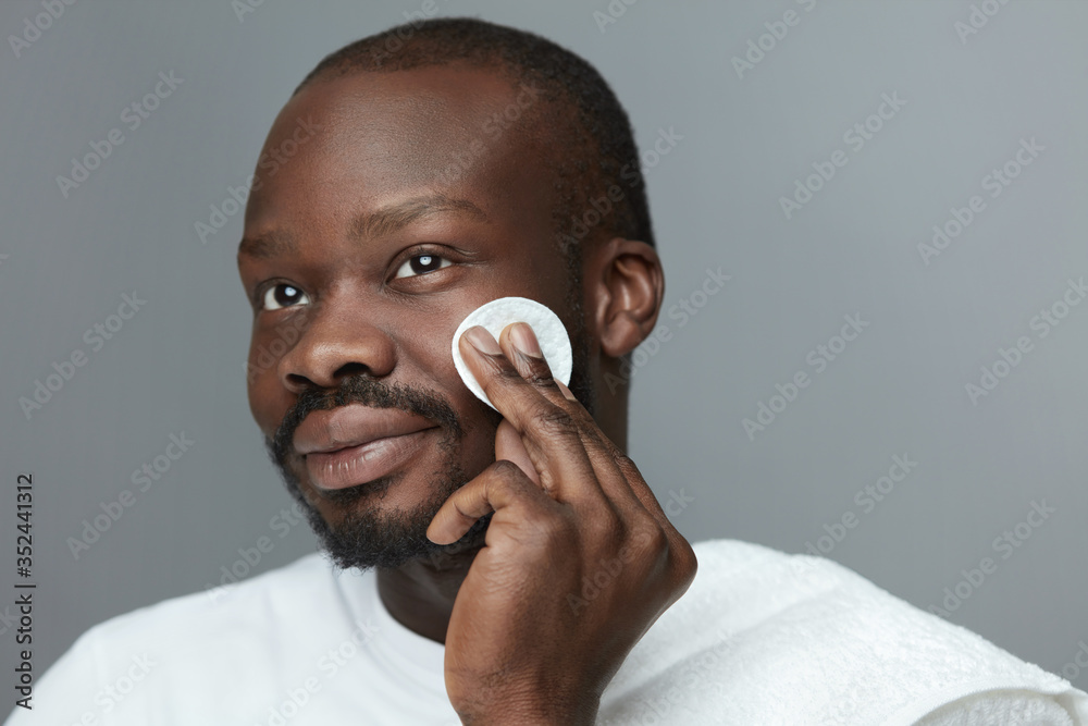 Fototapeta Face Skincare. Male African Model Cleans Facial Skin With Round Cotton Pad. Beauty Treatment Routine For Man.