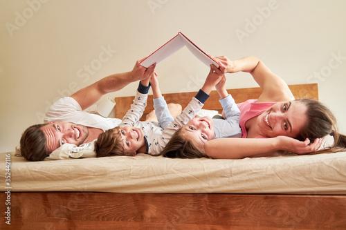 Fototapeta Familie mit zwei Kindern lesen ein Buch auf dem Bett obraz
