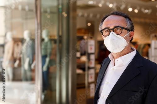 Obraz uomo con occhiali neri vestito elegante  e con mascherina facciale Kn95 davanti a un negozio nelle vie del centro - fototapety do salonu