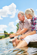 Senior Couple Fishing By The Lake In Summer