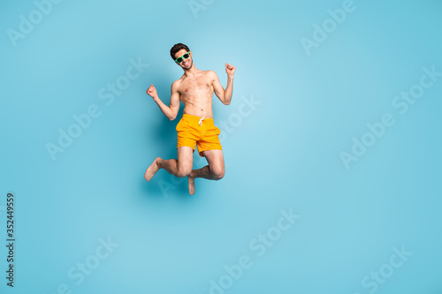 Obraz Full length body size view of his he nice attractive cheerful cheery guy in swimming shorts jumping having fun isolated on bright vivid shine vibrant green blue turquoise color background - fototapety do salonu