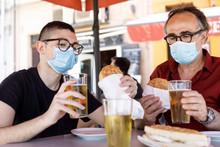 Padre E Figlio Seduti Nel Tavolino Di Un Bar Brindano Con Un Boccale, Di Birra Ma Protetti Da Una Mascherina Chirurgica
