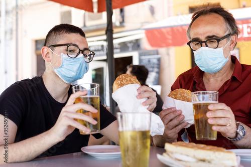 Foto padre e figlio seduti nel tavolino di un bar brindano con un boccale, di birra m
