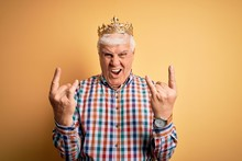 Senior Handsome Hoary Man Wearing Golden Crown Of King Over Isolated Yellow Background Shouting With Crazy Expression Doing Rock Symbol With Hands Up. Music Star. Heavy Concept.