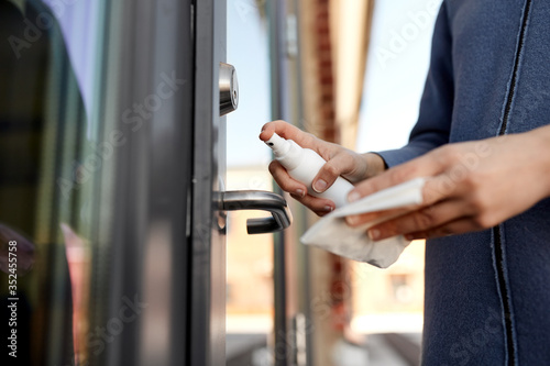 Obraz hygiene, health care and safety concept - close up of hands cleaning outdoor door handle surface with disinfectant spray and tissue - fototapety do salonu