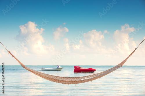 Obraz Empty hammock under tall palm trees on tropical beach - fototapety do salonu