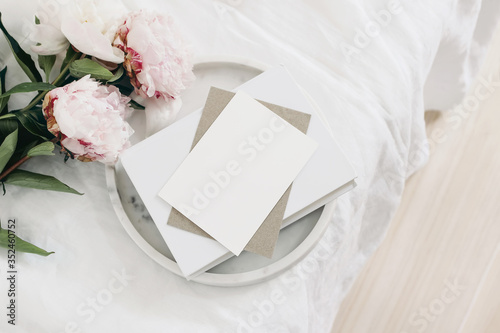 Fototapeta Wedding still life scene. Greeting card mockup scene, craft paper envelope, book on marble tray. Pink peony flowers on white linen table cloth. Vintage feminine styled photo, wooden floor. Flat lay. obraz