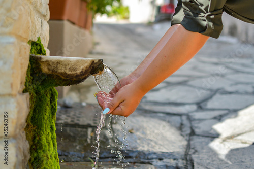 Valokuvatapetti Washing hands in fresh, cold, potable source water on a mountain, Drinking Sprin