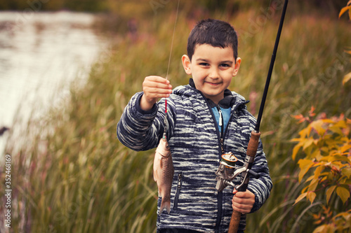 Cute boy catches fish on a summer lake Canvas Print