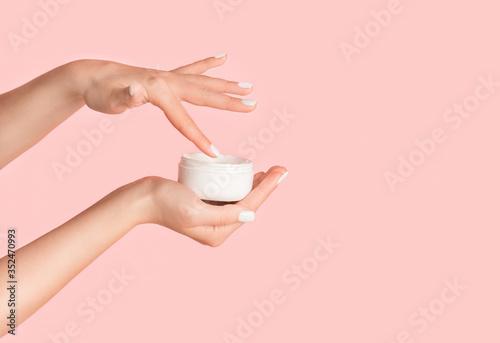 Slika na platnu Unrecognizable girl applying cream from jar onto her hands against pink backgrou