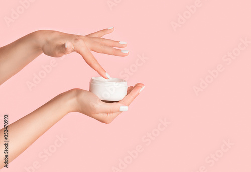 Fotografering Unrecognizable girl applying cream from jar onto her hands against pink backgrou