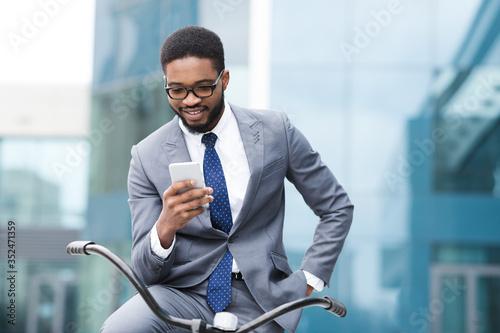 Fototapeta Handsome businessman texting on phone sitting on bike obraz