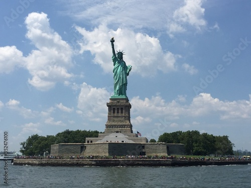 Fotografía Statue Of Liberty By River Against Cloudy Sky