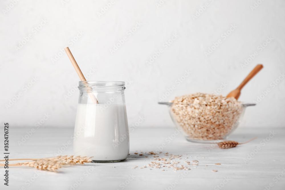 Fototapeta Jar of tasty oat milk on white table