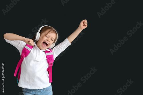 Obraz Cute little schoolgirl listening to music on dark background - fototapety do salonu
