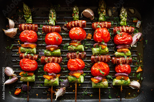 Fototapeta Grilled skewers of green asparagus, cherry tomatoes and sausage with the addition of herbs in a grill pan, top view obraz