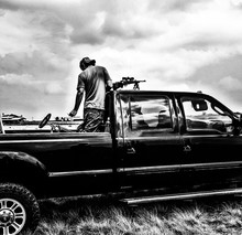 Man With Sniper On Pick-up Truck Against Sky
