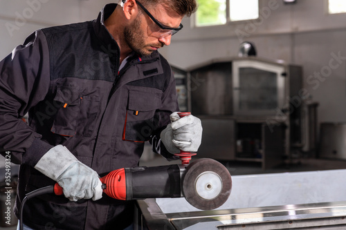 Fototapeta Industrial worker with angle grinder working and polishing stainless steel structure at workshop