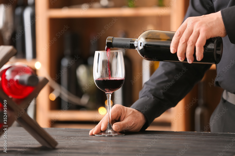 Fototapeta Man pouring tasty wine from bottle into glass in cellar