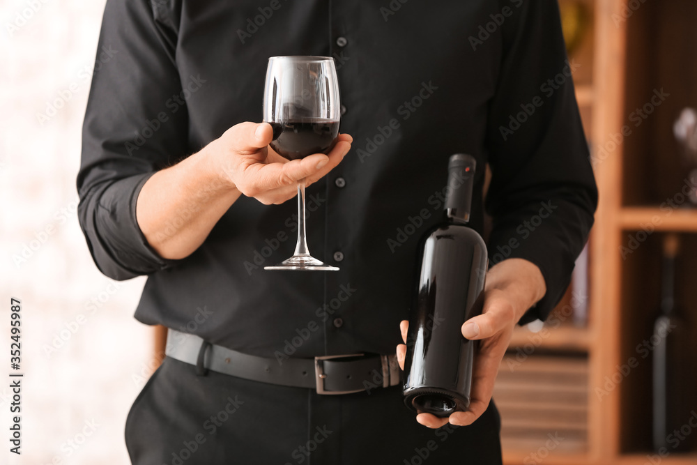Fototapeta Man with bottle and glass of tasty wine in cellar