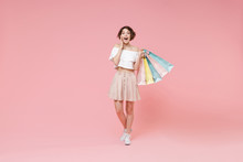 Shocked Young Woman Girl In Summer Clothes Hold Package Bag With Purchases Isolated On Pastel Pink Background Studio Portrait. Shopping Discount Sale Concept. Mock Up Copy Space. Put Hand On Cheek.
